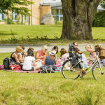 RONNEBY, SWEDEN - JULY 05, 2014: Several young women having picnic in the grass in public park.
